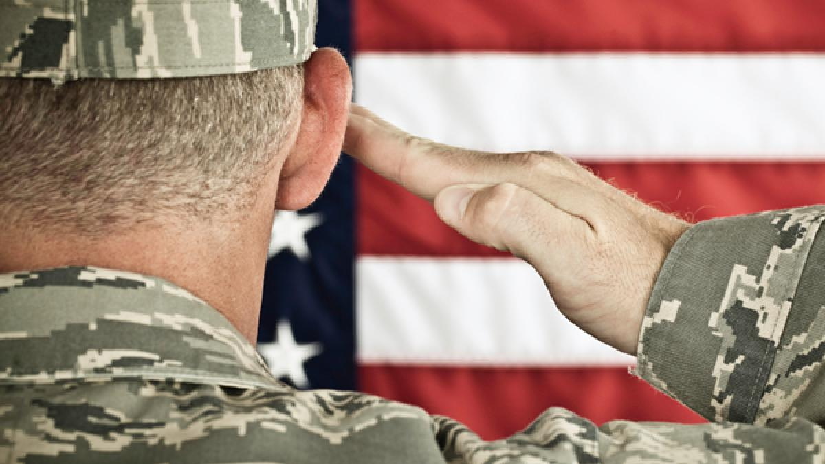 Military soldier saluting an American flag